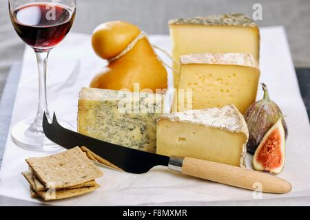 Assorted types of cheese with figs, crackers and a glass of port - Stock Photo