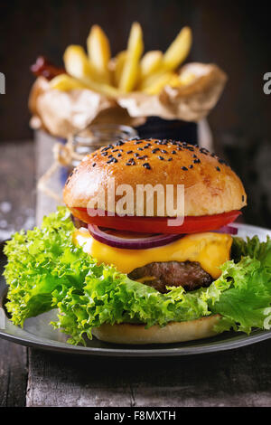 Fresh homemade burger with black sesame seeds on wooden cutting board with French fries, served with ketchup sauce - Stock Photo