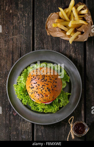 Fresh homemade burger with black sesame seeds in metal plate and fried potatoes in backing paper, served with ketchup - Stock Photo