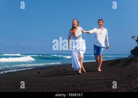 Happy newlywed family on honeymoon holidays - just married loving couple run with fun on sea black sand beach along - Stock Photo