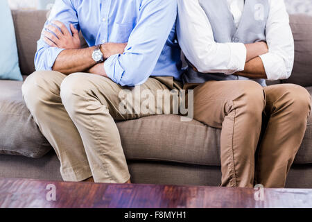 Gay couple sitting back-to-back after arguing - Stock Photo