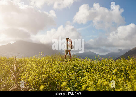Romantic young couple embracing and  looking at each other, while standing on a hill top outdoors on a summer day. - Stock Photo