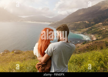 Romantic young couple embracing and looking at each other on a sunny day outdoors. Man and woman looking into each - Stock Photo