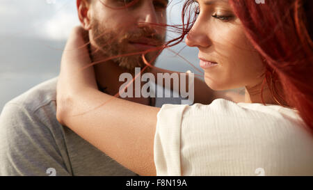 Close up shot of young woman with her boyfriend outdoors. Young couple on holiday. - Stock Photo
