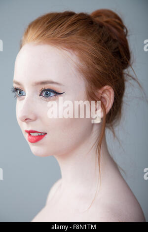 Portrait of a pretty redheaded woman with her hair tied up in a bun. - Stock Photo