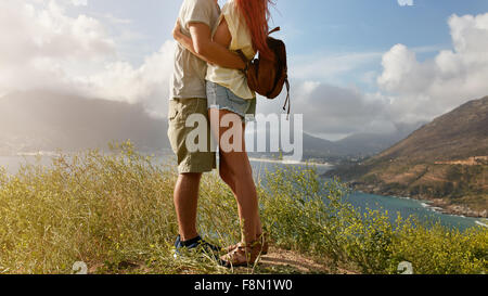 Cropped image of loving young couple embracing while standing on a cliff on coastline. Low section image of young - Stock Photo