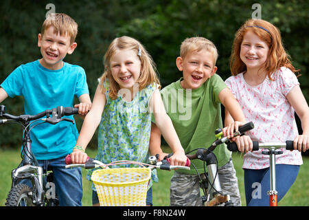Group Of Children Playing On Bikes And Scooter - Stock Photo