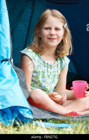 Girl Having Snack On Camping Trip - Stock Photo