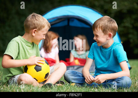 Two Boys Talking On Camping Trip - Stock Photo