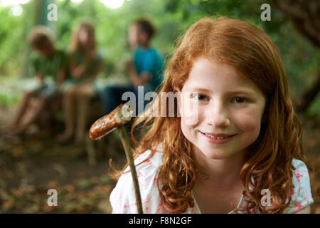 Girl Eating Sausage Cooked On Camp Fire With Friends - Stock Photo