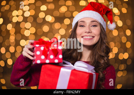 Cheerful pretty young woman in santa claus hat holding presents over holidays lights background - Stock Photo