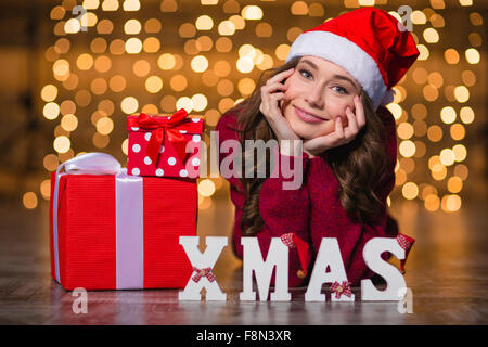 Beautiful happy young woman in santa claus hat  lying near decorated letters spelling word Xmas and christmas gifts - Stock Photo