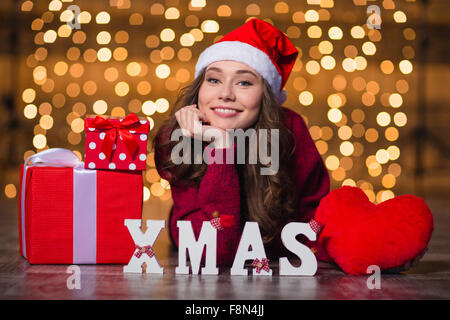 Cheerful beautiful girl in santa claus hat lying near letters spelling word Xmas over holidays lights background - Stock Photo