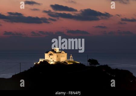 Chapel of Saint Nicholas on the hillside of Myrina city port lit at night at sunset. Lemnos or Limnos island, Greece. - Stock Photo