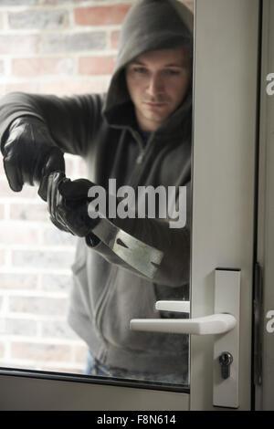 Burglar Using Crowbar To Break Into House - Stock Photo
