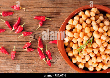 high-angle shot of an earthenware bowl with cooked chickpeas and some red chili peppers on a rustic wooden table - Stock Photo
