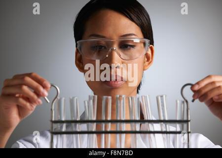 Female Scientist Examines Test Tubes - Stock Photo