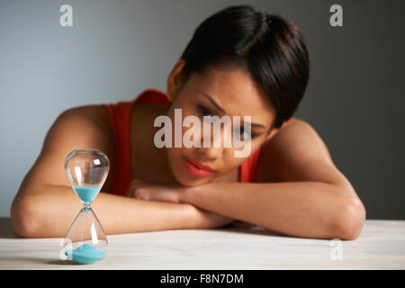 Sad Woman Looking At Hourglass - Stock Photo