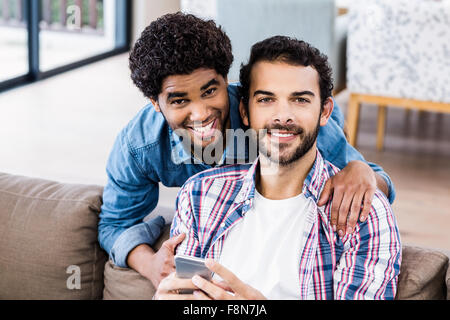 Happy gay couple using smartphone on sofa - Stock Photo