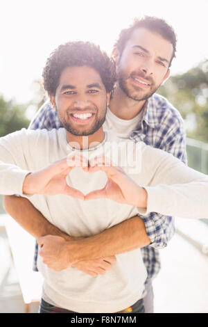 Happy gay couple hugging outdoors - Stock Photo