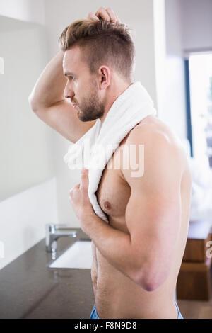 Handsome man looking in mirror - Stock Photo