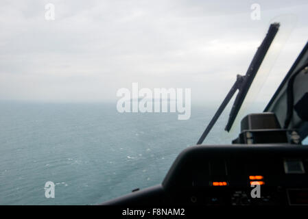 in the cockpit of a helicopter flying from the mainland to Lundy Island, on the horizon - Stock Photo