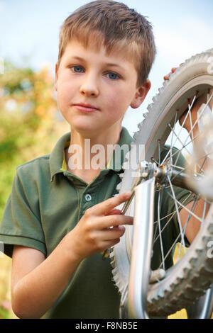 Boy Fixing Wheel Of Bike - Stock Photo