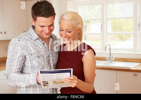 Young Couple Looking At Details For New Home - Stock Photo