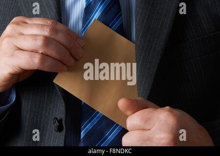 Businessman Putting Plain Brown Envelope In Jacket Pocket - Stock Photo