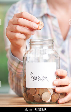 Woman Dropping Coins Into Jar Labelled Pension - Stock Photo
