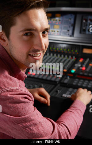 Engineer Working At Mixing Desk In Recording Studio - Stock Photo