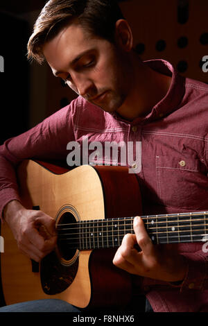 Man Playing Acoustic Guitar In Recording Studio - Stock Photo