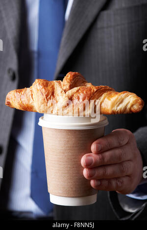 Businessman Holding Takeaway Coffee And Croissant - Stock Photo