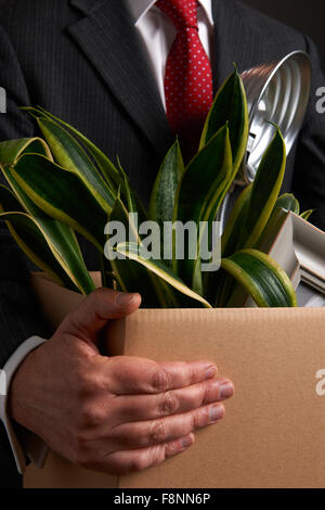 Redundant Businessman Carrying Possessions In Box - Stock Photo