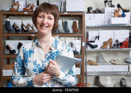 Owner Of Online Shoe Business Using Digital Tablet - Stock Photo