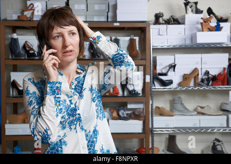 Worried Owner Of Shoe Store On Phone - Stock Photo