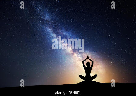 Milky Way. Night sky with stars and silhouette of a woman practicing yoga. - Stock Photo