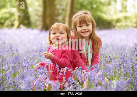 Two Girls Sitting In Bluebell Woods Together - Stock Photo