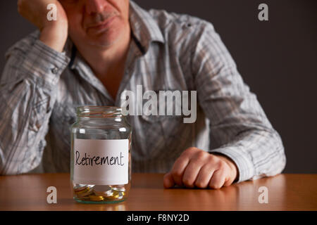 Depressed Man Looking At Empty Jar Labelled Retirement - Stock Photo