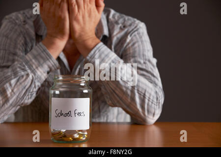 Man With Head In Hands Looking At Jar Labelled School Fees - Stock Photo