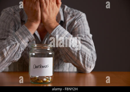 Man With Head In Hands Looking At Jar Labelled Christmas - Stock Photo