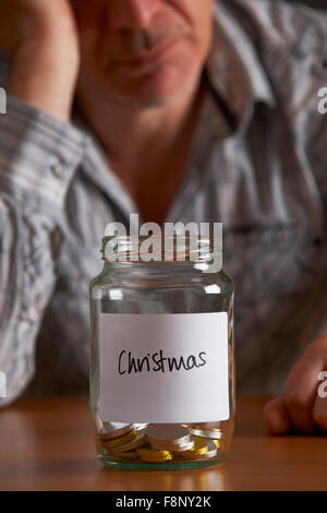 Depressed Man Looking At Empty Jar Labelled Christmas - Stock Photo
