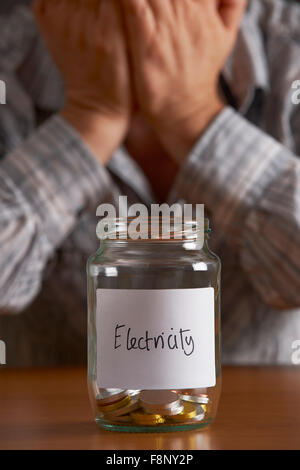 Man With Head In Hands Looking At Jar Labelled Electricity - Stock Photo