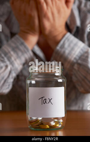 Man With Head In Hands Looking At Jar Labelled Tax - Stock Photo