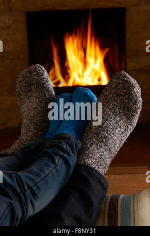 Father And Child Warming Feet By Fire - Stock Photo