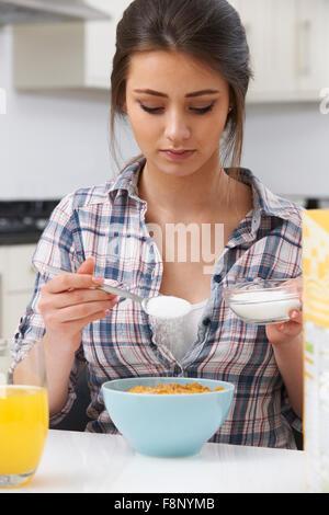 Teenage Girl Adding Sugar To Breakfast Cereal - Stock Photo