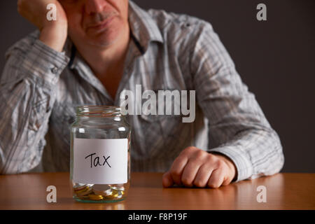 Depressed Man Looking At Empty Jar Labelled Tax - Stock Photo