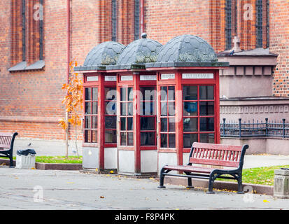 Street scene: row of three traditional style, old-fashioned faded roadside red telephone boxes in Kaunas, the second - Stock Photo