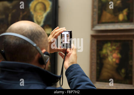 A man listening to an audio guide and taking pictures of The Four Seasons: Spring, Summer, Autumn and Winter, paintings - Stock Photo