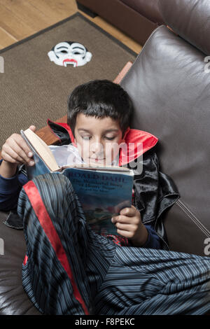 Boy,8,in Halloween outfit reading a book - Stock Photo